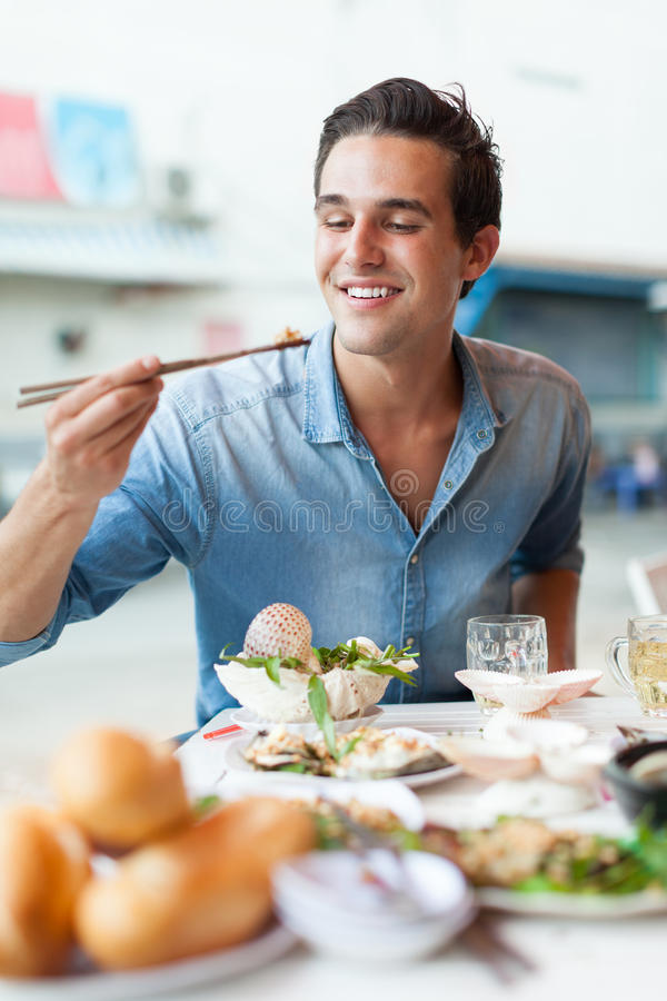Tourist man eating asian food street local cafe royalty free stock image