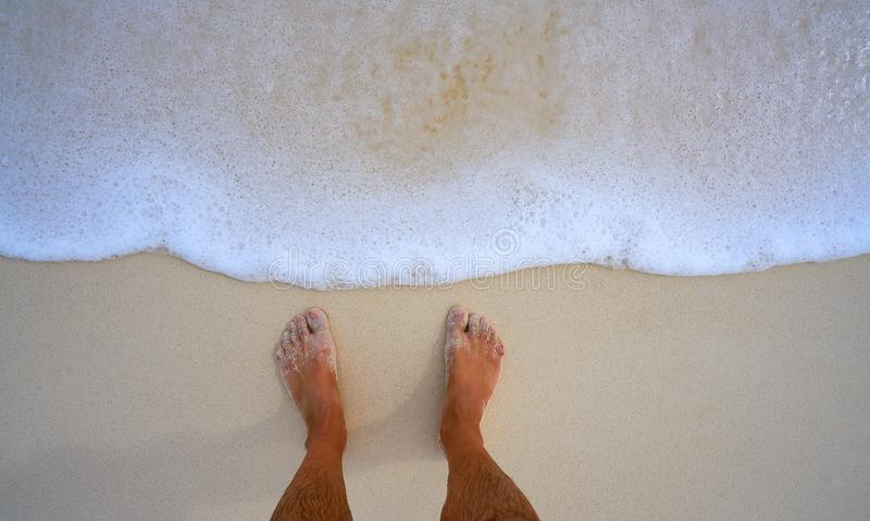 Tourist feet in tropical white sand beach royalty free stock photography