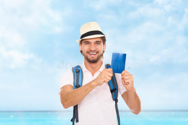 Tourist man holding passport, hat with backpack stock photo