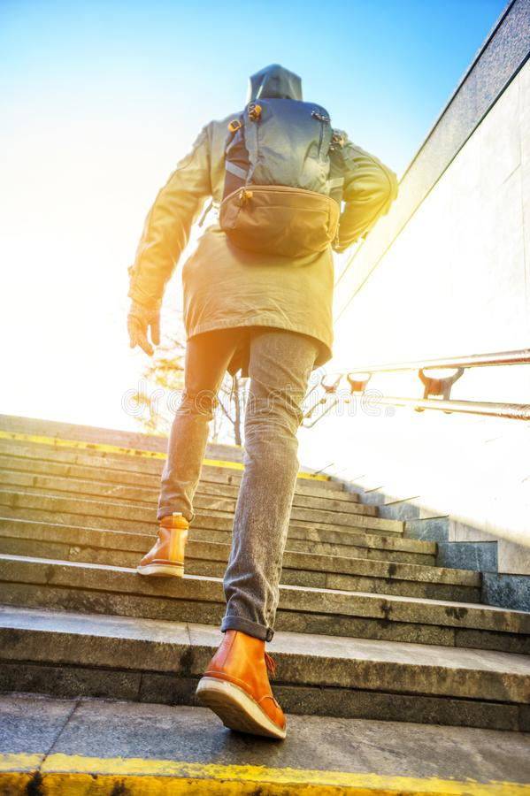 Tourist in urban environment. Tourist man in a hood with a large backpack climbs the stairs at dawn in an urban environment. Tourist in winter city concept stock photos