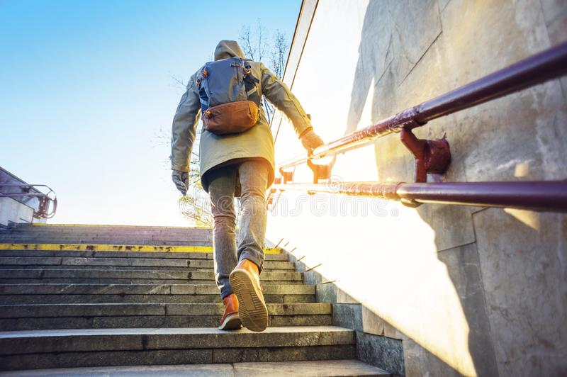 Tourist in urban environment. Tourist man in a hood with a large backpack climbs the stairs at dawn in an urban environment. Tourist in winter city concept royalty free stock photos