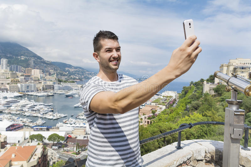 Tourist man making selfie in Monaco,France. Tourist man making selfie on a picturesque city landscape background in Monaco,France royalty free stock photo