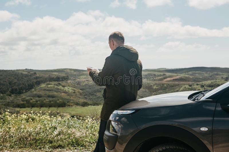 A tourist man next to the car looks at the map of the area for further travel.  royalty free stock images
