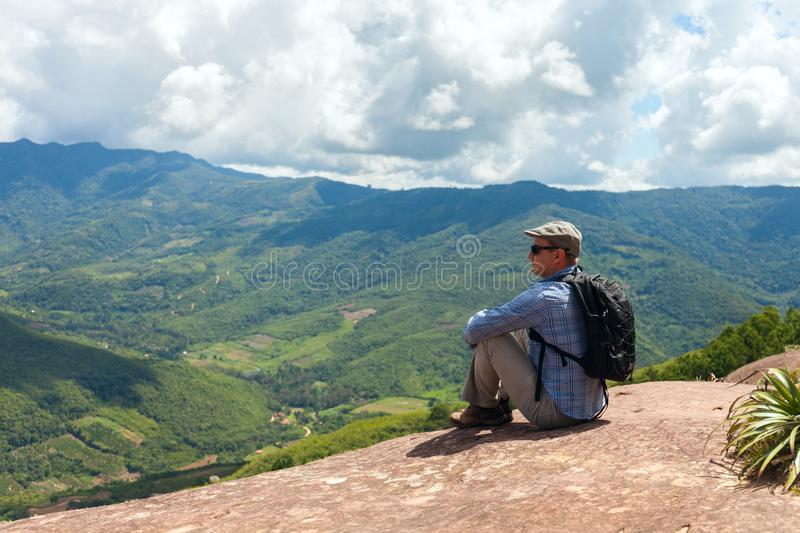 Tourist man sits on a cliff edge on the top of mountain with gorgeous view at stunning valley in the subtropical part of Bolivia. Samaipata. Stock photo stock photography