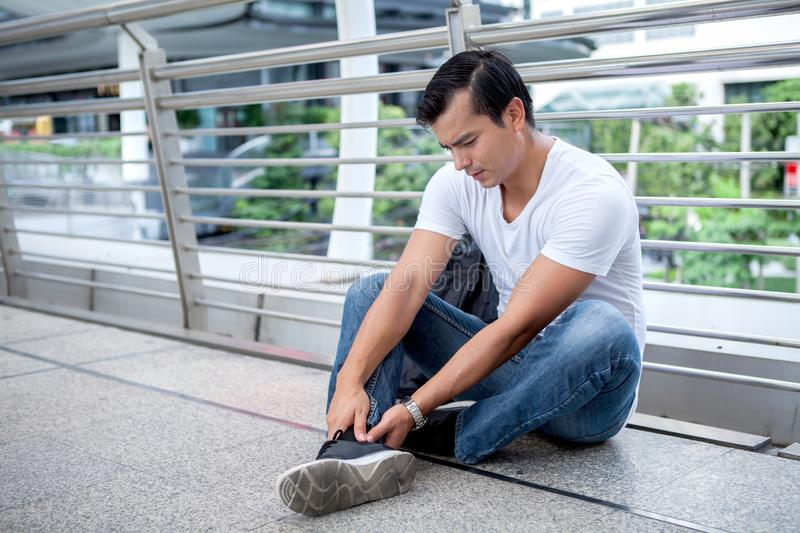 Tourist man sitting on floor take off the shoes massaging feet walking a lot of foot pain after a long walk royalty free stock photography