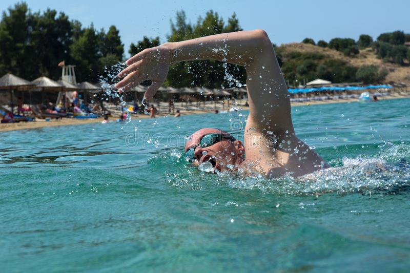 Tourist man in swimming sports glasses is floating in the Aegean Sea on the coast of Sithonia Peninsula stock photo