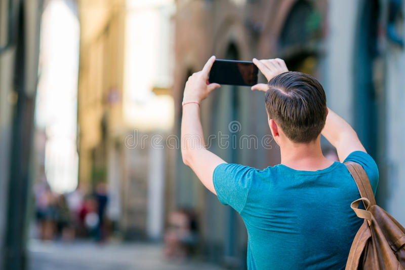 Tourist man taking photo by smartphone in hands walking along the narrow italian streets in Europe. Young urban boy on. Boy caucasian with smartphone walking in stock photos