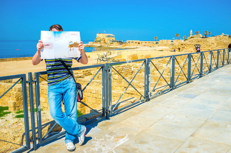 The tourist with a map. CAESARIA, ISRAEL - MAY 19, 2016: The tourist explores the map of the archaeological site, standing among the ancient ruins, on May 19 in stock photos