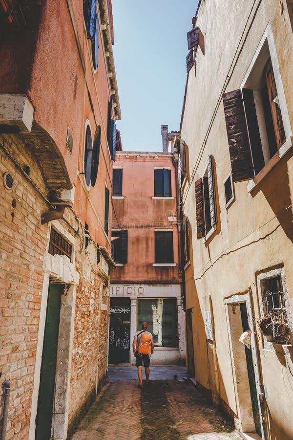 Tourist mit einem orange Rucksack und einem Bandana geht entlang schmale Straße in Europa Italien Venedig im Sommer Die Fassade v lizenzfreie stockfotos