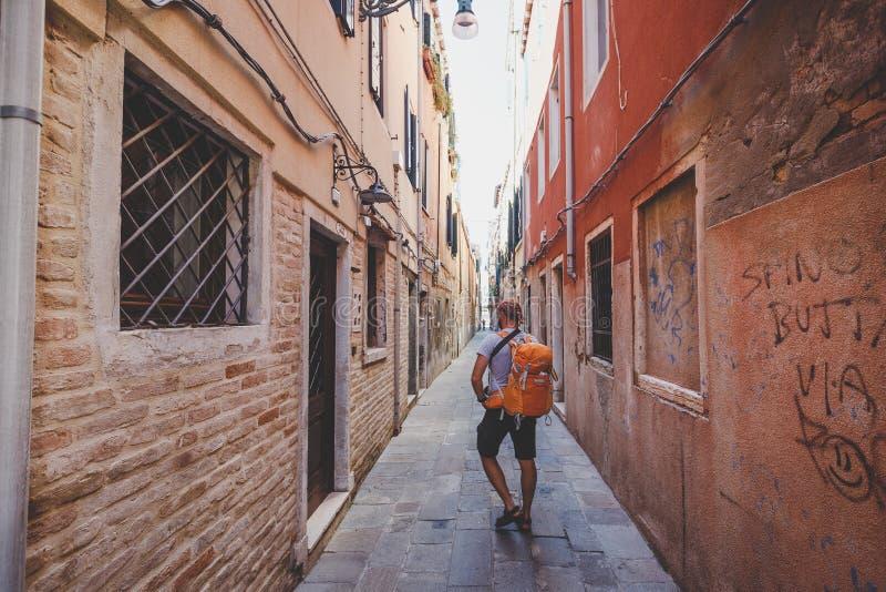 Tourist mit einem orange Rucksack und einem Bandana geht entlang schmale Straße in Europa Italien Venedig im Sommer Die Fassade v stockfoto