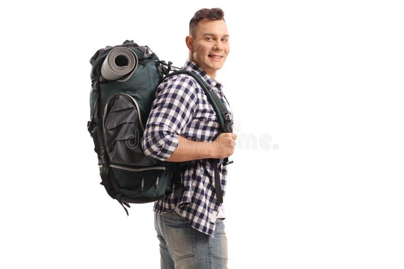 Tourist mit einem Rucksack, der die Kamera und das Lächeln betrachtet lizenzfreies stockfoto