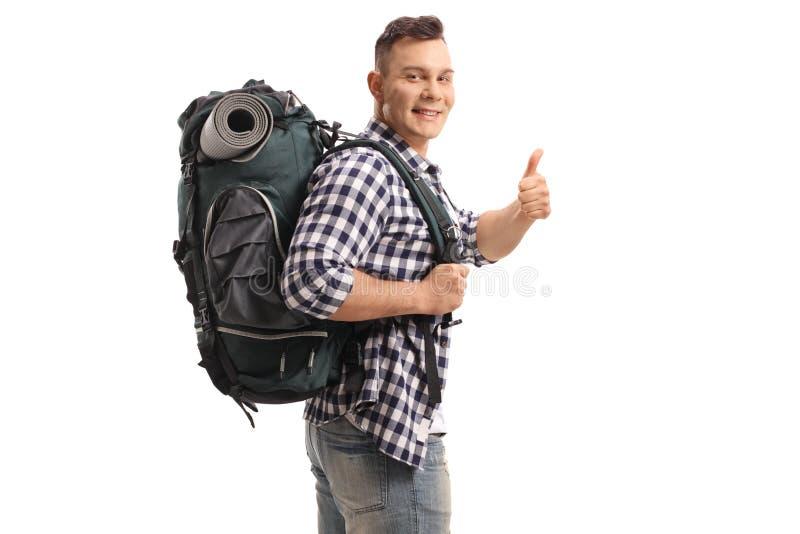 Tourist mit einem Rucksack, der einen Daumen herauf Geste herstellt lizenzfreies stockbild