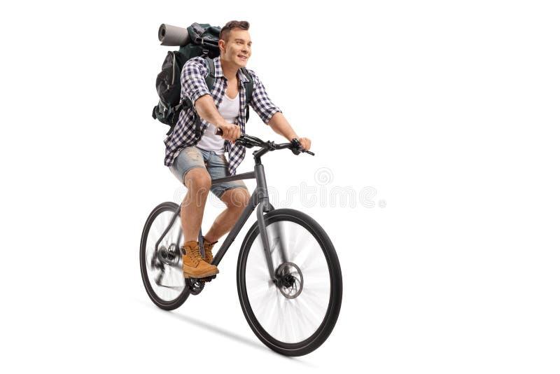 Tourist mit einem Rucksack, der Fahrrad fährt lizenzfreie stockbilder