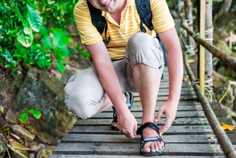 Tourist mit einem Rucksack macht oben Sandalen Reißverschluss zu lizenzfreies stockbild