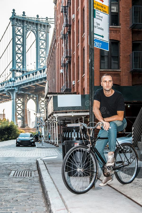 Tourist model enjoying New York City and Dumbo, Brooklyn. Tourist handsome model posing on a bike and Manhattan Bridge between Manhattan and Brooklyn over East royalty free stock photo
