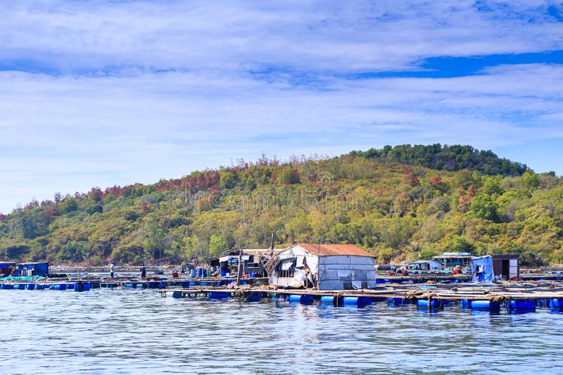 Tourist Moorage by Green Coast in Vietnam Clouds Sky. Closeup Vietnamese tourist moorage near green hills coast against white clouds lace in blue sky royalty free stock photos