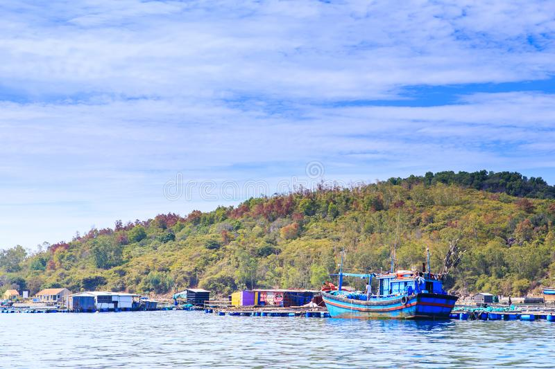 Tourist Moorage by Green Coast in Vietnam Clouds Sky. Vietnamese tourist moorage near green hills coast against white clouds lace in blue sky royalty free stock image