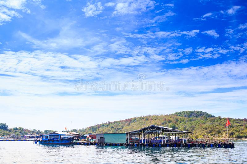 Tourist Moorage Vietnamese Banners by Green Coast Clouds Sky. Tourist moorage with Vietnamese national banners near green hills coast against white clouds lace stock photography