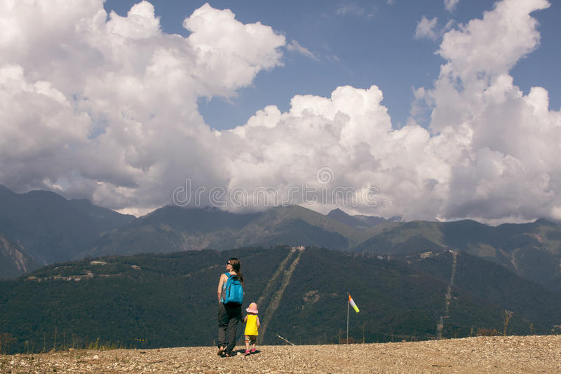 Tourist mother and daughter walking in the mountain views. summer sunny day. horizontal picture stock photo