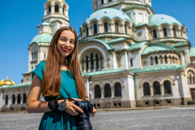 Tourist near the St. Alexander Nevsky Cathedral. Young woman tourist standing with photo camera near the St. Alexander Nevsky Cathedral in Sofia, the capital of stock photo