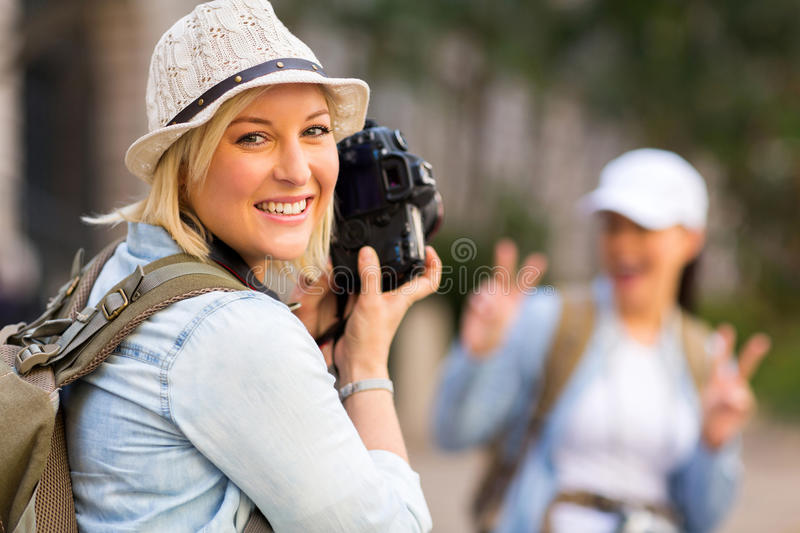 Tourist photo friend. Happy young tourist taking a photo of her friend with digital camera royalty free stock images