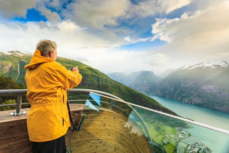 Tourist photographer with camera on Stegastein lookout, Norway. Tourism and travel. Male tourist nature photographer taking photo with camera, enjoying Aurland stock images
