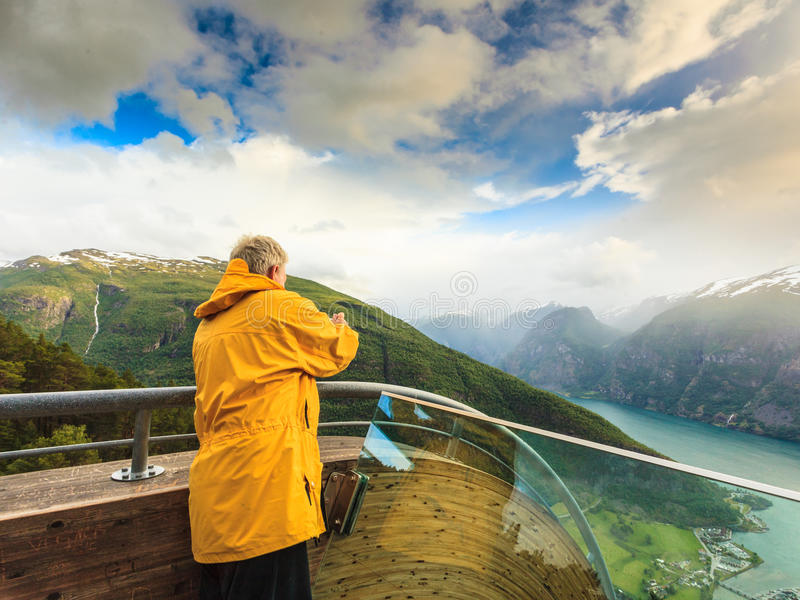 Tourist photographer with camera on Stegastein lookout, Norway. Tourism and travel. Male tourist nature photographer taking photo with camera, enjoying Aurland stock photography