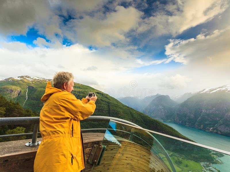 Tourist photographer with camera on Stegastein lookout, Norway. Tourism and travel. Male tourist nature photographer taking photo with camera, enjoying Aurland royalty free stock photos