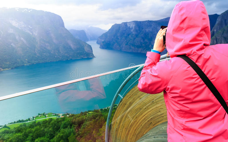 Tourist photographer with camera on Stegastein lookout, Norway. Tourism and travel. Woman tourist nature photographer taking photo with camera, enjoying Aurland royalty free stock image