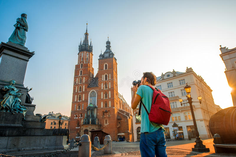 Tourist photographing in the center of Krakow. Male tourist with backpack photographing famous Polish basilica in the center of Krakow stock photography