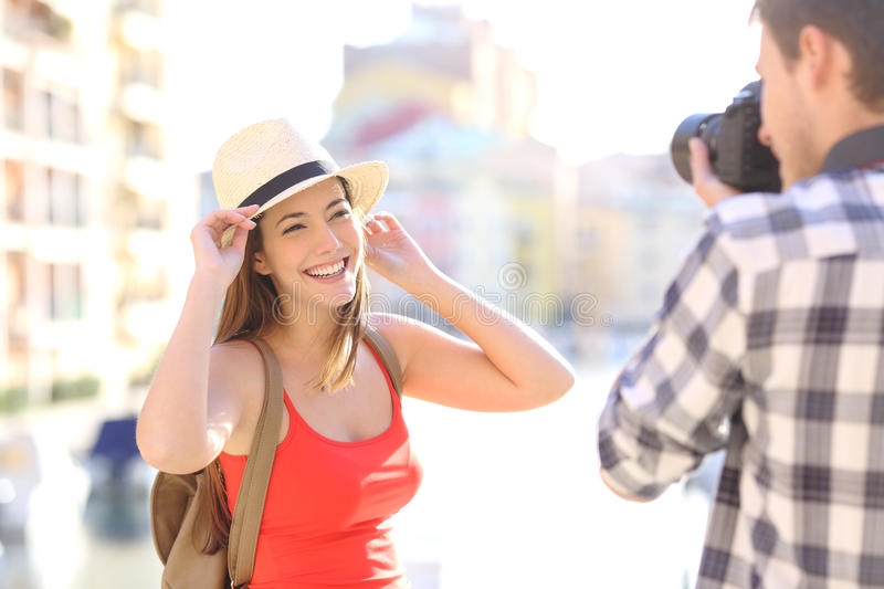 Tourist photographing his friend on vacations. Tourist photographing his girlfriend wearing red shirt in a travel destination on vacations royalty free stock photo