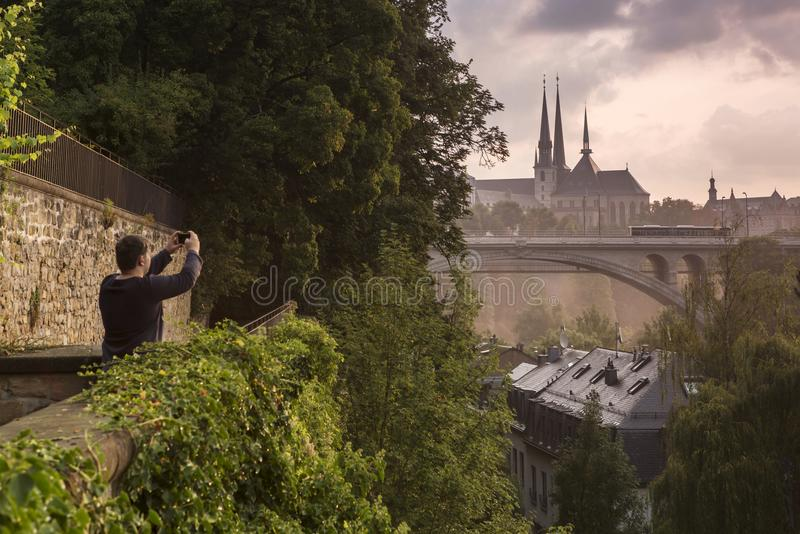 Tourist photographing Luxembourg city. Man photographing with mobile phone the landmarks of Luxembourg city, from Hollerich: Adolphe bridge and Notre Dame royalty free stock photo