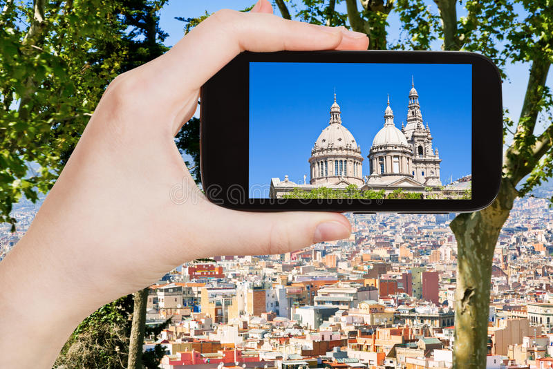 Tourist photographs of Barcelona skyline. Travel concept - tourist takes picture of National Art Museum of Catalonia and Barcelona skyline on smartphone, Spain royalty free stock image