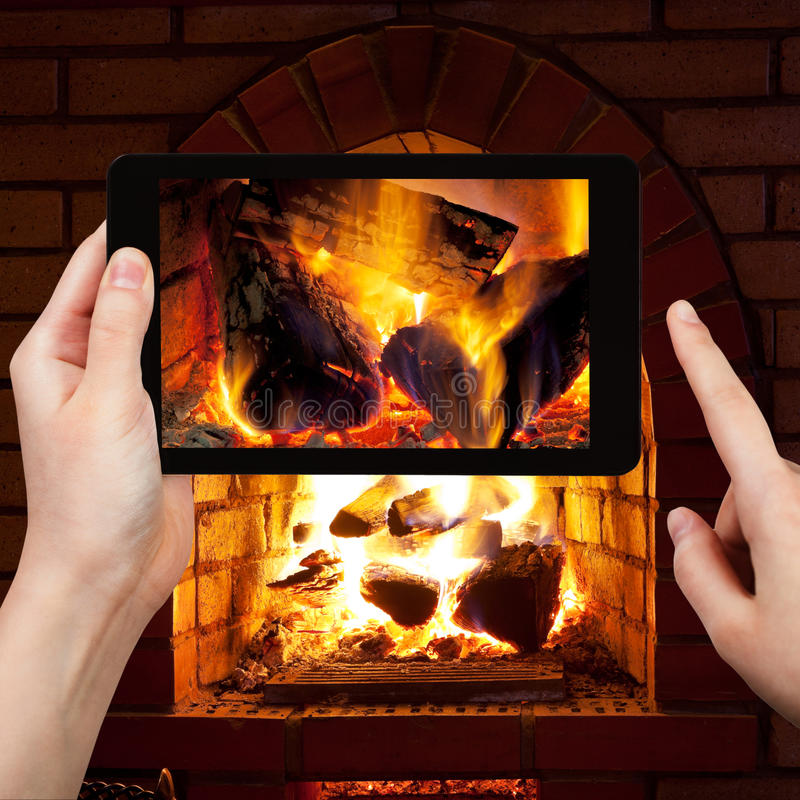 Tourist photographs of fire in fireplace stock image