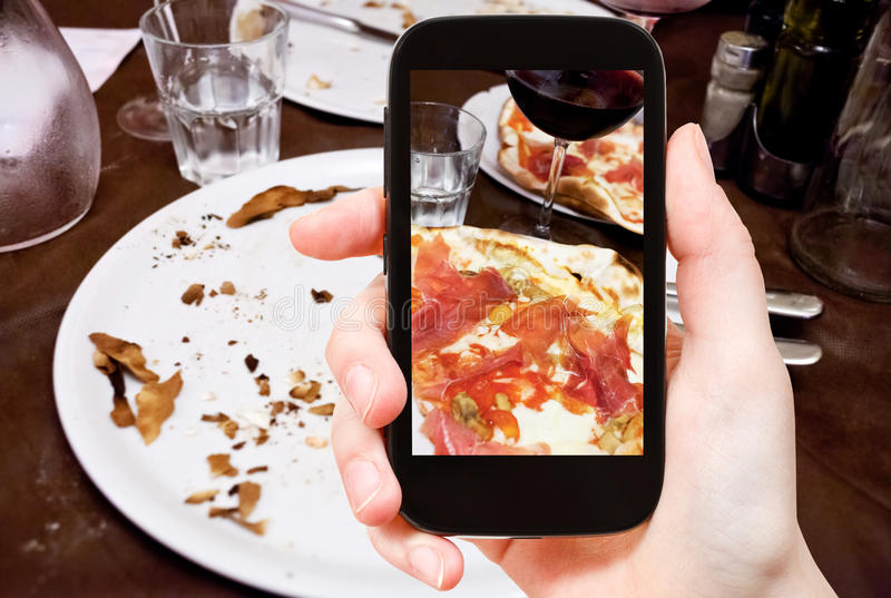 Tourist photographs italian pizza with parma ham royalty free stock photography
