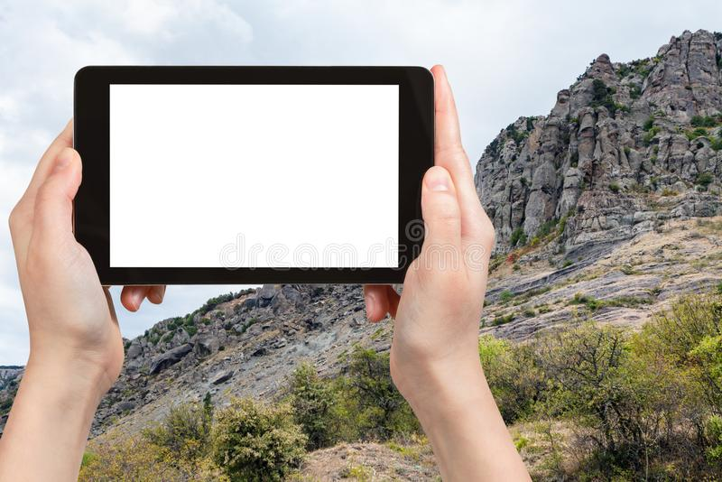 Tourist photographs rocks at Demerdzhi Mountain. Travel concept - tourist photographs old rocks at Demerdzhi (Demirci) Mountain from The Valley of Ghosts on royalty free stock images