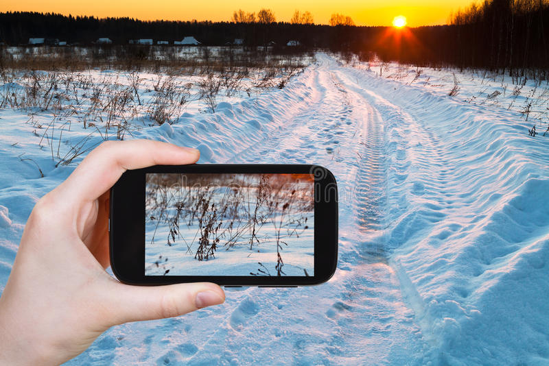 Tourist photographs of sunset over snowy field royalty free stock photo