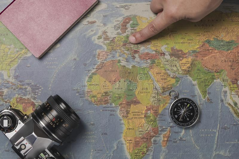 Tourist planning vacation with the help of world map with other travel accessories around. Young woman pointing at North Europe on. The world map. Pointing the stock image