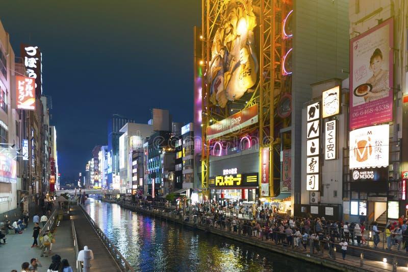 Tourist popular night shopping scene in Osaka City at Dotonbori Namba area with illuminated neon signs and billboards along the ri. Osaka, Japan - April 2016 royalty free stock photo