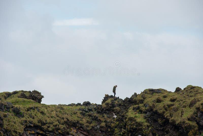 Tourist posing on the Londrangar basalt cliff, Iceland royalty free stock photography