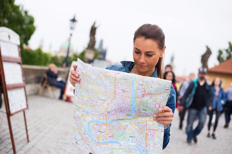 Tourist in Prague. Young woman reading a map in prague royalty free stock images