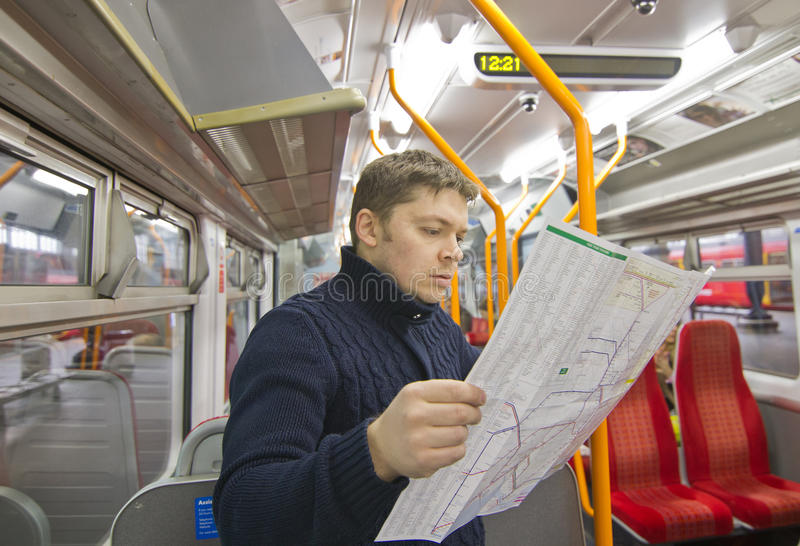 Tourist reading map. Tourist man reading map in train stock image