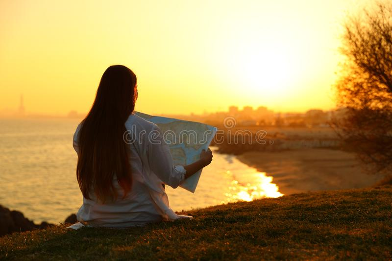 Tourist reading a map searching location. Back view backlight portrait of a tourist reading a map searching location sitting on the grass at sunset stock image