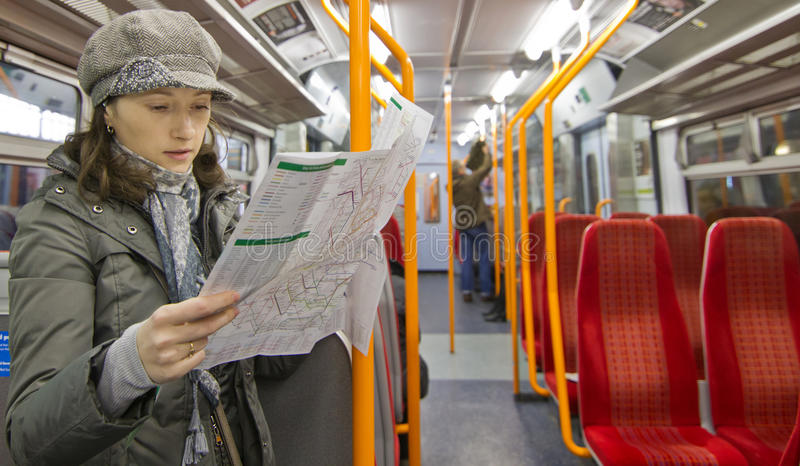 Tourist reading map. Tourist woman reading map in train royalty free stock photography