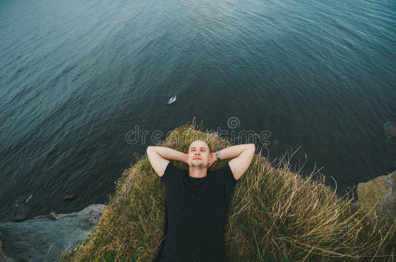 Tourist resting on grass on Baltic sea background. Top view royalty free stock photos