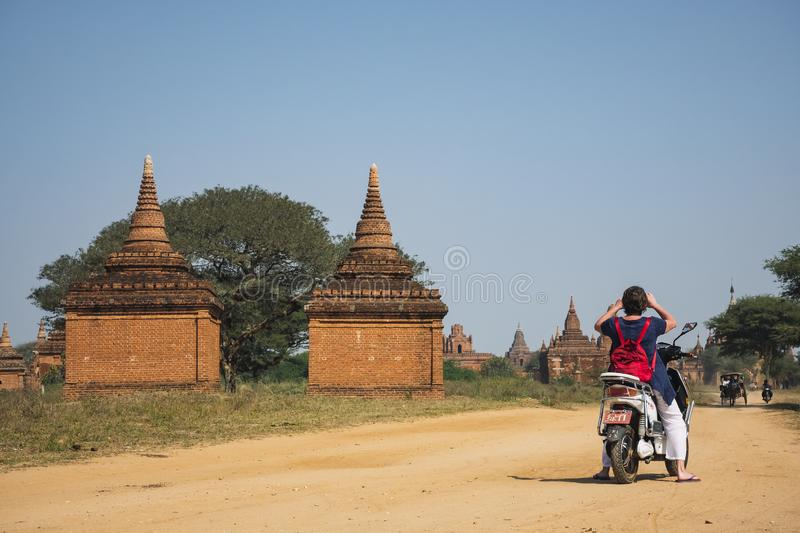 Tourist ride electric bicycle take picture landscape of Bagan Historical Pagoda Travel Asia royalty free stock photography