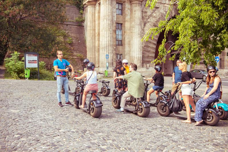 Tourist rides a electric scooter on old square sightseeing europe stock images