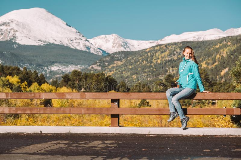 Tourist in Rocky Mountains at autumn, Colorado, USA. Woman tourist sitting on fence. Season changing from autumn to winter. Rocky Mountains, Colorado, USA royalty free stock images
