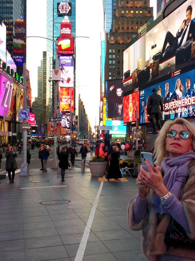Tourist in Times Square, NYC, NY, USA. A tourist`s sunglasses reflect the bright lights in Times Square, New York City. This photo was taken on February 12th stock photos