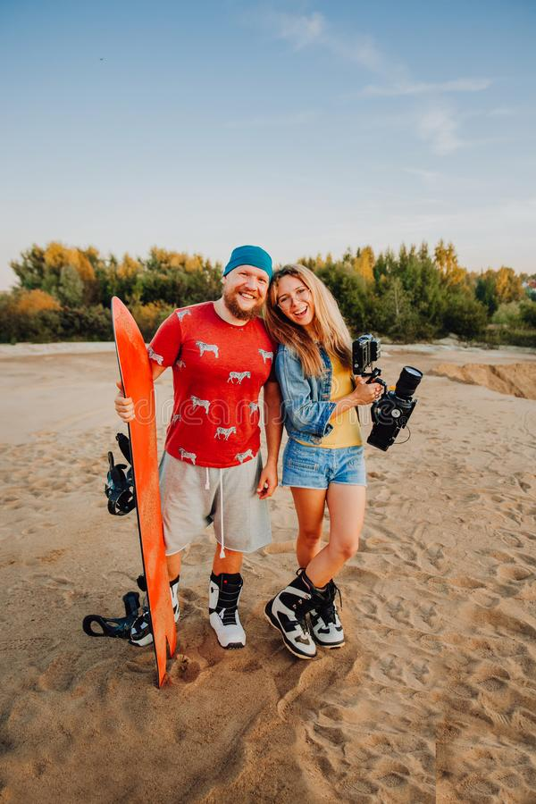 Tourist Sandboarding in the Desert a Man and a woman shoot a movie with a professional camera stock photos